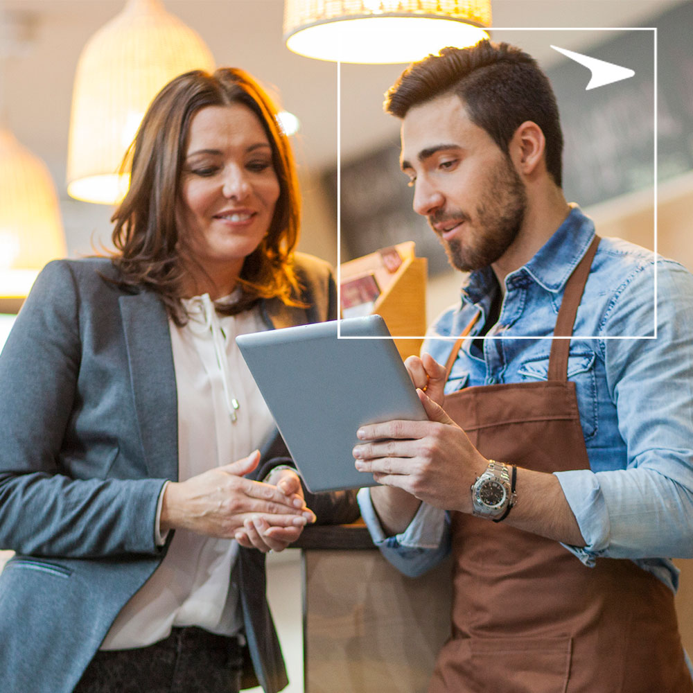 Woman in suit and man in apron looking at tablet in restaurant
